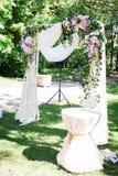 El aire abierto adornó el área para la ceremonia de boda con un arco de madera adornado con las flores frescas y el material beig Imágenes de archivo libres de regalías