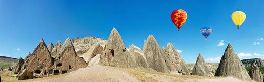 El aire caliente colorido hincha volar sobre los acantilados volcánicos en Cappadocia, Anatolia, Turquía Foto de archivo libre de regalías