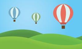 El aire caliente colorido tres hincha volar sobre el paisaje con g Fotos de archivo