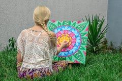 El aire libre de pintura, una mujer joven rubia dibuja una mandala en la naturaleza que se sienta en la hierba ilustración del vector