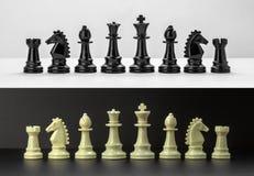 El ajedrez blanco y negro figura en fondo blanco y negro Foto de archivo libre de regalías