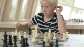 El ajedrez de los juegos de ni?os El muchacho juega con los pedazos blancos metrajes