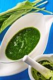 El ajo salvaje se va con la sopa del mortero y del ajo en la placa blanca en el fondo de madera azul, forma de vida sana, hierba  Fotografía de archivo
