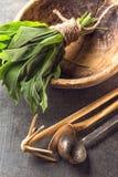 El ajo salvaje se va en cuenco de madera con los accesorios de la cocina en el fondo de piedra gris, forma de vida sana, hierba e Fotografía de archivo