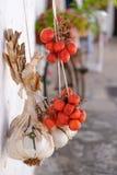 El ajo y los tomates rojos brillantes colgaron hacia fuera para secarse fuera de una casa en Alberobello, Puglia, Italia foto de archivo