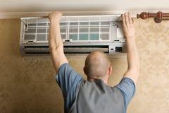 El ajustador fija un nuevo acondicionador de aire Imagen de archivo