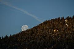 El ajuste de la Luna Llena detrás de la montaña Imagenes de archivo