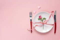 El ajuste festivo de la tabla con los cubiertos, poco subió y los corazones en el pi Imagenes de archivo