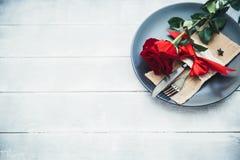 El ajuste festivo de la tabla para el día del ` s de la tarjeta del día de San Valentín con la bifurcación, cuchillo y subió Fotografía de archivo