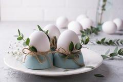 El ajuste festivo de la tabla de Pascua con el pollo blanco eggs en las hueveras, puntillas de la hoja del eucalipto Imagen de archivo