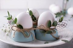 El ajuste festivo de la tabla de Pascua con el pollo blanco eggs en las hueveras, puntillas de la hoja del eucalipto Imagenes de archivo