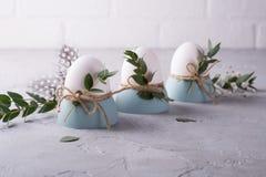 El ajuste festivo de la tabla de Pascua con el pollo blanco eggs en las hueveras, puntillas de la hoja del eucalipto Imágenes de archivo libres de regalías