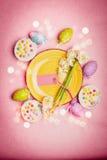 El ajuste precioso de Pascua en color en colores pastel con la decoración eggs, las flores, las tortas e iluminación del bokeh en Fotografía de archivo