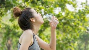 El ajuste sano del deporte lindo asiático y la muchacha adolescente delgada firme beben el agua Foto de archivo