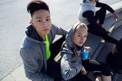 El ajuste y los jóvenes deportivos combinan la relajación después de se resuelven en la ciudad Imagen de archivo libre de regalías