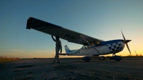 El ala de un aeroplano está consiguiendo examinada por un aviador de sexo masculino en un fondo de la puesta del sol almacen de metraje de vídeo