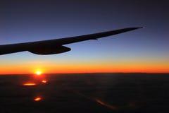 El ala del aeroplano con advierten y el cielo de los colores del frío, luz hermosa de la salida del sol Imagen de archivo libre de regalías