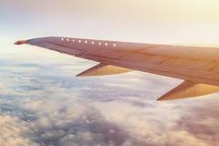 El ala del aeroplano en cielo con las nubes y el sol brillan Imágenes de archivo libres de regalías