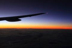 El ala del aeroplano en vuelo, advierte y los colores fríos a través de ventana Fotografía de archivo