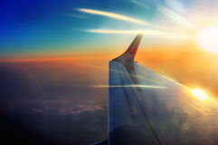 El ala del aeroplano en vuelo en salida del sol emite Fotos de archivo