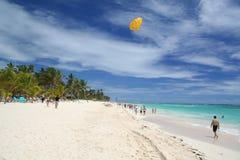 El ala flexible amarilla cuelga sobre persona que toma el sol en la playa del Caribe blanca Fotos de archivo libres de regalías
