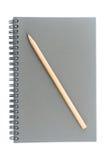 El alambre limita o tuerce en espiral - sketchbook encuadernado hecho del lápiz gris del tablero y de madera aislado en el fondo  Imagenes de archivo
