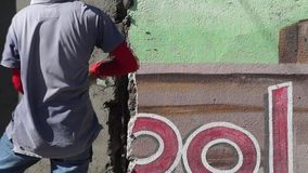 El albañil de sexo masculino enmascarado de la construcción lanza el cemento en la pared metrajes