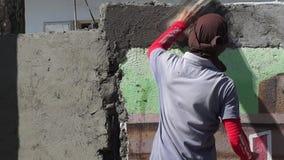 El albañil de sexo masculino enmascarado de la construcción lanza el cemento en la pared almacen de video