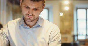 El alcanzar en un ciertas noticias en línea antes del trabajo Hombre de negocios joven que se sienta en café de la ciudad usando  almacen de metraje de vídeo