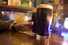 El alcanzar hacia fuera para una cerveza de malto Imágenes de archivo libres de regalías
