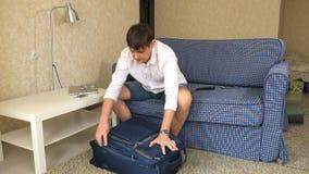 El alcohólico del marido recoge cosas en una maleta y cremalleras él El divorcio metrajes