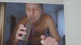 El alcohólico sin la camiseta bebe el alcohol de una botella en el armario en casa sofá triste en abuso de alcohol y alcoholismo almacen de video