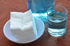 El alcohol azul para el lavado hiere en el algodón blanco de cristal y limpio Imagenes de archivo