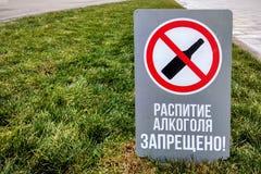 El alcohol de consumición prohibió firma en ruso en césped verde foto de archivo libre de regalías