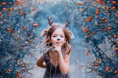 El alcohol del bosque bajo la forma de niño en un vestido marrón claro, un ciervo del bebé lleva juguetónamente en el bosque, fotos de archivo