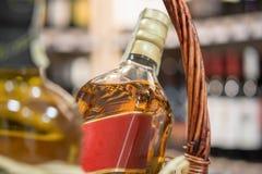 El alcohol en la cesta arregló en la tabla delante de empañado detrás imagen de archivo