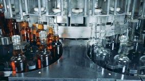 El alcohol está consiguiendo vertido en las botellas por la máquina de la fábrica metrajes