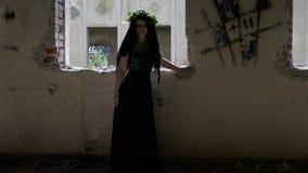 El alcohol vengativo de una mujer en vintage negro viste la situación cerca de una ventana arruinada de la casa que se derrumba v almacen de metraje de vídeo