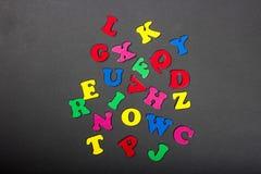 El alfabeto coloreado brillante pone letras a colocación en un fondo gris Imagen de archivo libre de regalías