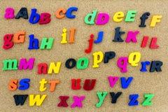 El alfabeto del tablero del corcho pone letras a colores Imagenes de archivo