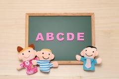 El alfabeto letra ABCDE, las muñecas de los niños y la muñeca del hombre en la pizarra Concepto inglés de la educación Imagen de archivo libre de regalías