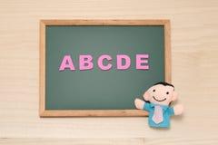 El alfabeto letra ABCDE y la muñeca del hombre en la pizarra Concepto inglés de la educación Foto de archivo libre de regalías