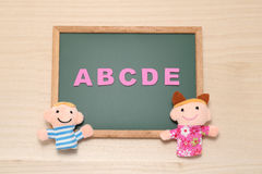 El alfabeto letra ABCDE y las muñecas de los niños en la pizarra Concepto inglés de la educación Fotos de archivo libres de regalías