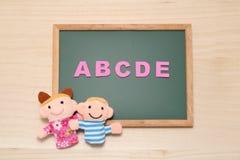 El alfabeto letra ABCDE y las muñecas de los niños en la pizarra Concepto inglés de la educación Imagenes de archivo