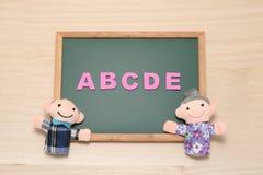 El alfabeto letra ABCDE y las muñecas mayores en la pizarra Concepto inglés de la educación Fotografía de archivo libre de regalías