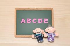 El alfabeto letra ABCDE y las muñecas mayores en la pizarra Concepto inglés de la educación Imagen de archivo