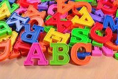 El alfabeto plástico coloreado pone letras a ABC Imagenes de archivo