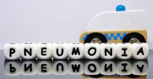 El alfabeto pone letras a deletrear una pulmonía de la palabra Fotos de archivo libres de regalías