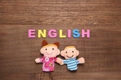 El alfabeto pone letras a INGLÉS y a las muñecas de los niños en la madera Foto de archivo libre de regalías