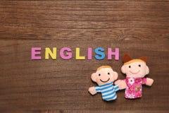 El alfabeto pone letras a INGLÉS y a las muñecas de los niños en la madera Imagenes de archivo